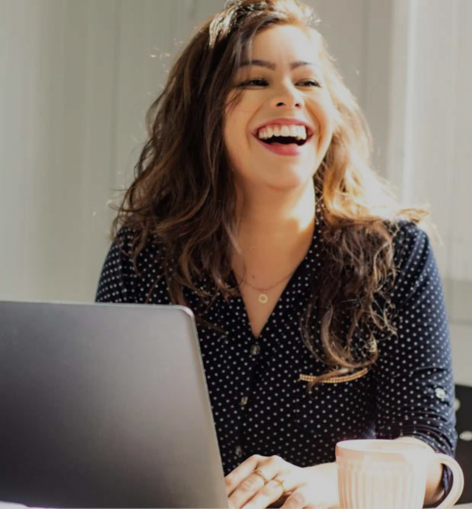 Photo of woman laughing while working on laptop