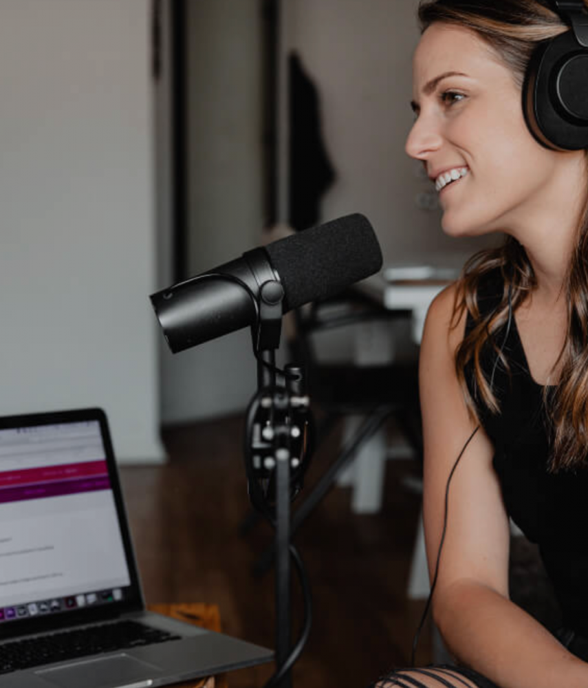 Photo of woman speaking into microphone for podcast.