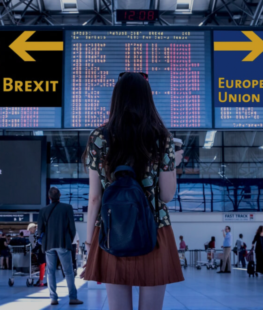 Photo of woman standing at the airport looking at a sign that displays Brexit and European Union