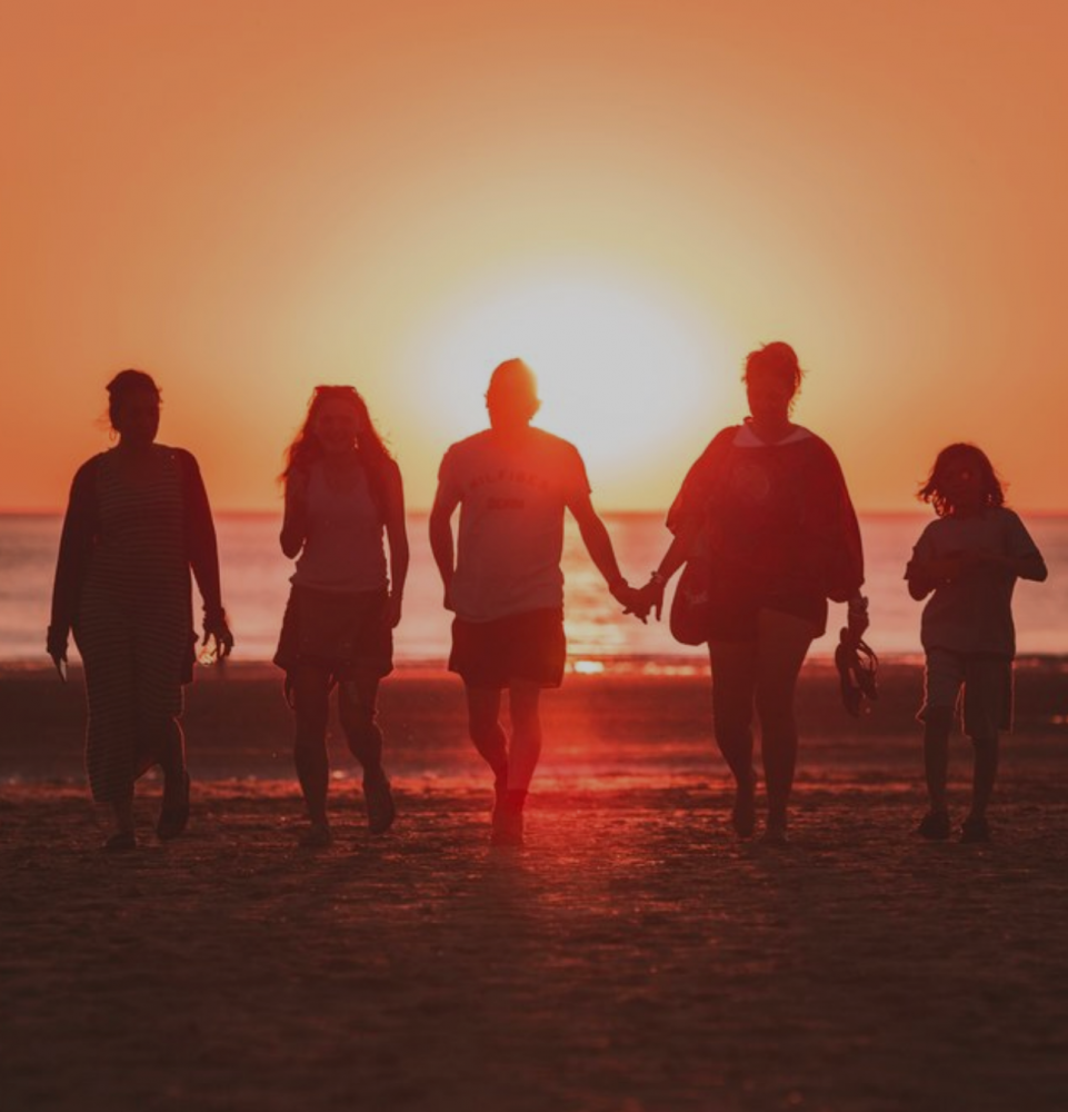Photo of friends on a beach with the sunset.